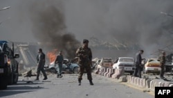 An Afghan security force member stands at the site of a massive car bomb attack in Kabul on May 31.