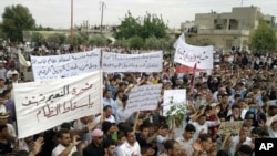 Antiregime protesters carry banners during a rally in Talbiseh, in the central Syrian province of Homs, last month.