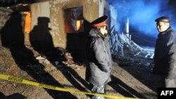 Полицейские у разрушенного дома на месте спецоперации против подозреваемых боевиков-исламистов в поселке Арашан вблизи Бишкека. 5 января 2011 года.