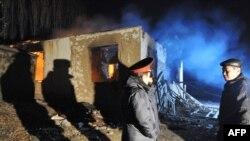 Полицейские у разрушенного дома на месте спецоперации против подозреваемых боевиков-исламистов в поселке Арашан вблизи Бишкека. 5 января 2011 года