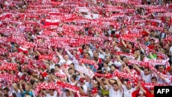 Polish football fans cheer their team in the Warsaw fanzone during Poland's game with Greece on June 8.