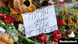 """Ukraine -- Bunches of flowers and poster """"Putin, world had not excuse"""" are near the embassy of the Netherlands in memory of killed people, Kyiv, 21Jul2014"""