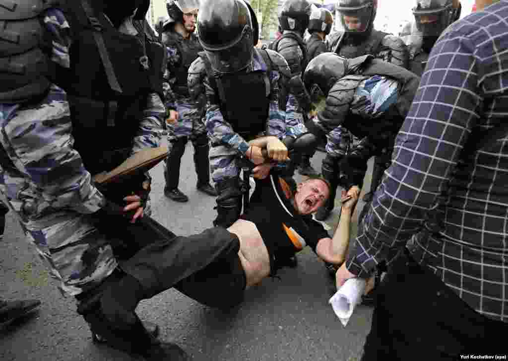 Russian police officers detain a participant at an opposition rally on Tverskaya Street in central Moscow on June 12. Opposition leader and anticorruption blogger Aleksei Navalny called on his supporters to hold a protest on Tverskaya Street, which leads to the Kremlin, instead of the site authorized by Moscow officials. Navalny was sentenced to 30 days in jail and 1,150 protesters were detained. (epa/Yuri Kochetkov)