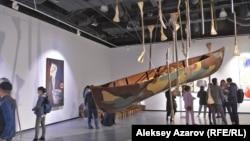 Композиционным центром выставки работ Арыстанбека Шалбаева является инсталляция «Дождь» – подвешенная лодка в окружении весел с лопастями из костей животных. Алматы, 8 мая 2019 года.