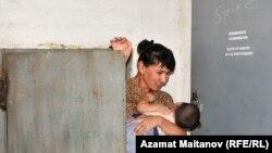 Жительница микрорайона Алмагуль из-за неработающего лифта перебирается по чердаку дома до своей квартиры. 17 августа 2010 года.