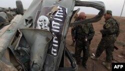 """قوات من البيشمركة يتفحصون سيارة مدمرة لمسلحي تنظيم """"داعش"""" بعد قصف أميركي شمال الموصل"""