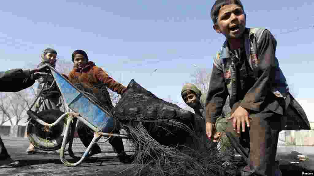 Afghan boys remove a burned tire from a Kabul street after a demonstration on February 22.