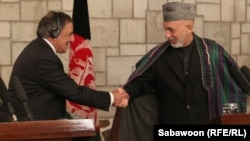 U.S. Defense Secretary Leon Panetta (left) shakes hands with Afghanistan President Hamid Karzai in Kabul on December 13.