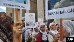 Курдски жени носат слики на затворени новинари пред почетокот на судењето на 44 новинари за поврзаност со курдските бунтовници.