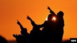 Люди наблюдают закат на турецко-сирийской границе. Иллюстративное фото.