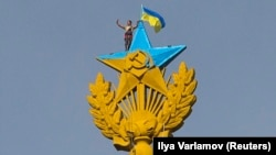 A worker takes a selfie as he stands with a Ukrainian flag on a Soviet-style star in Moscow on August 20.