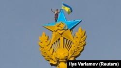 Верхолаз робить «селфі» поруч з перефарбованою радянською зіркою та українським прапором, Москва, 20 серпня 2014 року