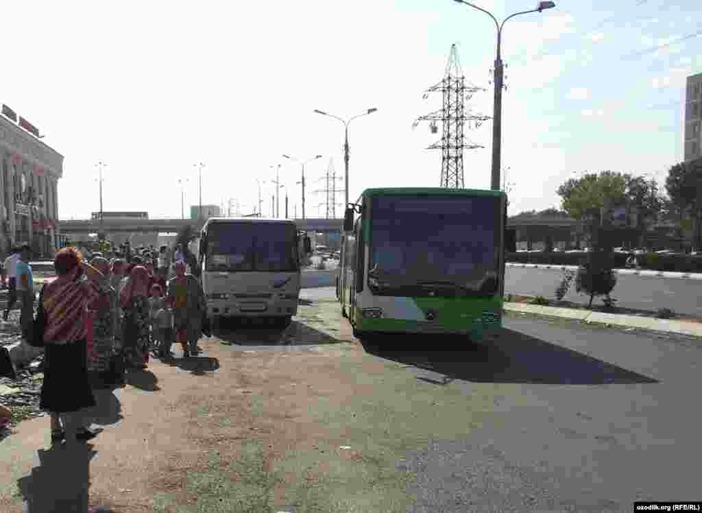 Travelers wait at a bus stop in Tashkent. With public buses rerouted to carry workers to the cotton fields, fewer are running their regular routes, meaning longer waits.