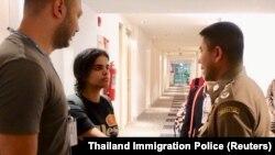 Сауд Арабиясының азаматы Рахаф Мохаммед әл-Кунун (сол жақтан екінші) Бангкок әуежайында Таиланд иммиграция қызметінің басшыларымен кездесіп тұр. 7 қаңтар 2019 жыл.