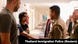 Рахаф Муҳаммад ал-Қунун Бангкок аэропортида Таиланд расмийлари билан.