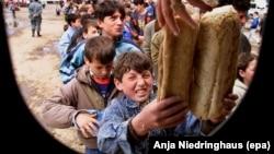 Një fëmijë refugjat shqiptar i Kosovës duke marrë bukë në qendër të Kukësit më 20 prill të vitit 1999