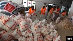 Pakistani workers of the Falah-e Insaniat Foundation in Karachi pack food to be distributed among people affected by the 7.7-magnitude earthquake in Balochistan. Foreign aid agencies have had their offers of aid rejected.