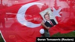 Сторонник президента Турции Реджепа Тайипа Эрдогана несет его портрет, Стамбул, июнь 2018 года.