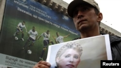 An opposition supporter holds a photo of former Prime Minister Yulia Tymoshenko in front of a billboard for Euro 2012 in Kyiv.