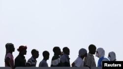 Migranți așteptînd să debarce de pe vasul italian Cigala Fulgosi în portul sicilian Augusta, Italia, 3 septembrie 2015