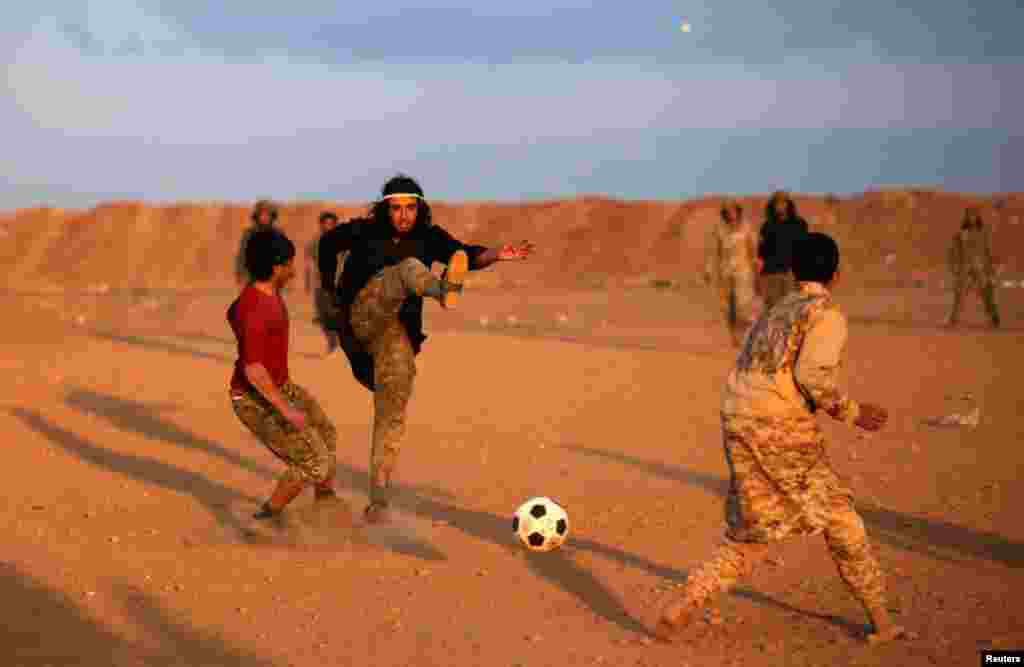 Free Syrian Army fighters play soccer in the northern Syrian town of Al-Rai. (Reuters/Khalil Ashawi)