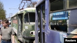 A man walks past damaged trams at the scene of one of the explosions in Dnipropetrovsk.