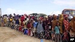 Somalezët presin në rend, prapa telit me gjemba, për të marrë ndihma ushqimore.