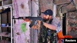 Iranian religious singer Hamid Reza Alimi points a rifle while on a trip to Syria.