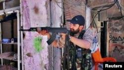 Iranian religious singer Hamid Reza Alimi points a rifle while on a trip to Syria.