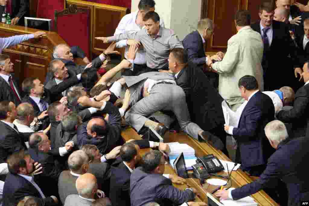 "A brawl erupts among balding politicians inside Kyiv's parliament in May 2012 during a ""hearing"" on a bill dealing with the use of the Russian language in Ukraine's east."