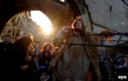 Жінка в костюмі відьми бере участь у параді під час святкування Вальпургієвої ночі в центральній Празі, Чеська Республіка, наприкінці дня 30 квітня 2014 року