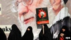 Аятолла Али Хаменеинин портрети алдында шиит диниятчы Нимр ал-Нимрдин сүрөтүн көтөргөн иран аялдары. Тегеран, 4-янваоь, 2016