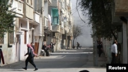 People run for cover from smoke after a shelling in the Karm al-Zeitoun area in Homs, Syria.