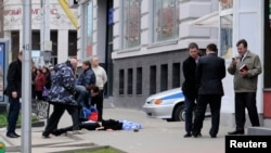 Investigators inspect the body of one of several victims killed by a gunman in Belgorod, Russia on April 22.