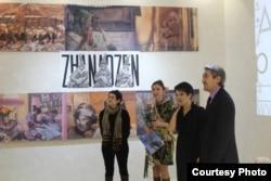 """Художница Сауле Сулейменова (вторая слева) на своей выставке. В центре - картина """"Три невесты"""" на фоне слов """"Жанаозен""""."""