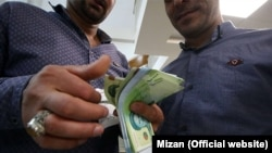 A currency dealer in Tehran counting rial banknotes. File photo