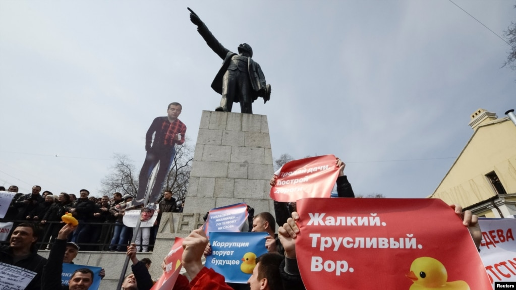 Opposition supporters hold posters and a cutout figure depicting Prime Minister Dmitry Medvedev during a rally in front of a monument of Soviet state founder Vladimir Lenin in Vladivostok on March 26, 2017.