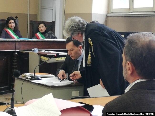 Свідок, італійський дипломат Фабріціо Романо (сидить) та адвокат захисту Раффаелле Делла Валле