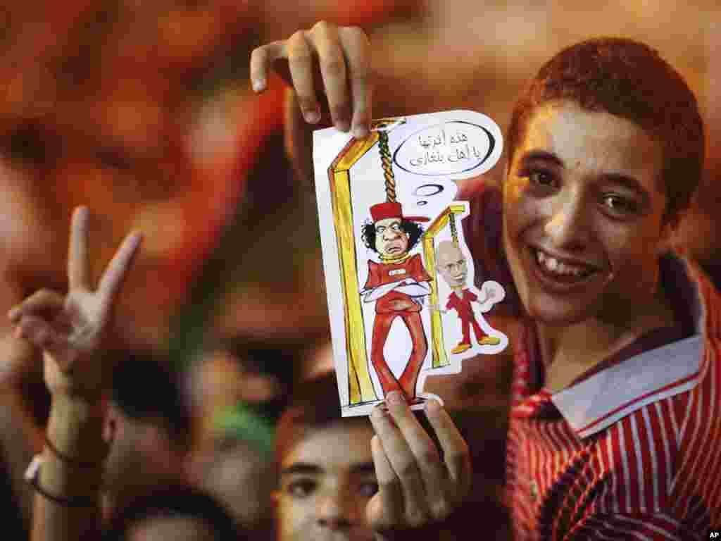 A boy in Benghazi holds a drawing depicting Qaddafi and his son Saif al-Islam being hanged.