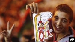 Ливийский мальчик показывает рисунок, где лидер страны Муаммар Каддафи и его сын Саиф аль-Ислам изображены повешенными. Бенгази, 22 августа 2011 года.