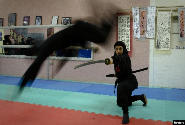 A female Ninjutsu practitioner jumps over a sword as members of various schools showcase their skills to the media in their gym, northwest of Tehran, in February 2012.