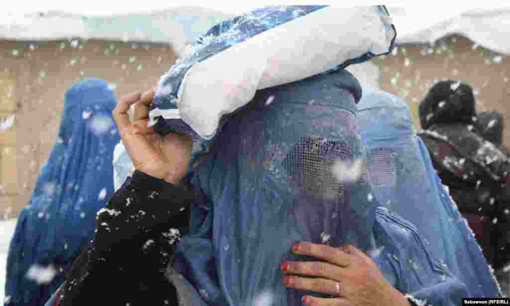 A woman carries a package she received at the aid distribution point.