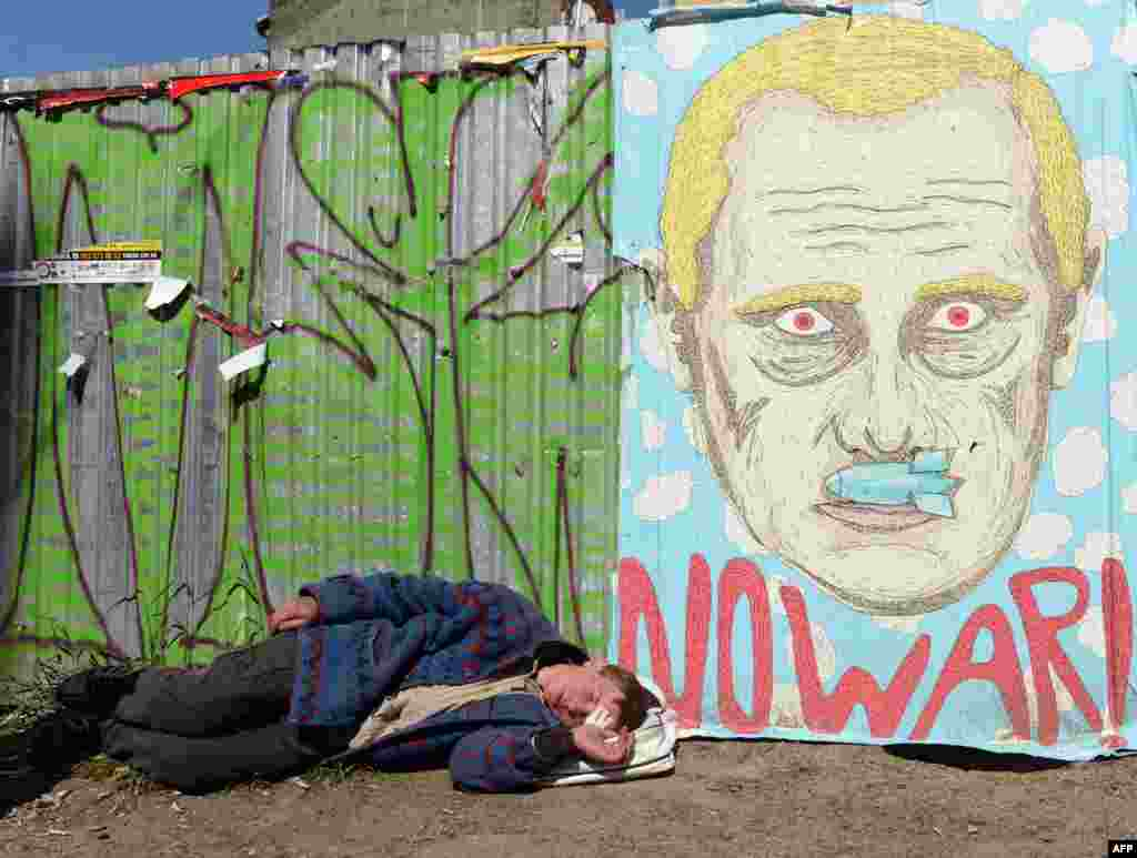 A man sleeps under an antiwar poster depicting Russian president Vladimir Putin with a bomb as a mustache in the center of the western Ukrainian city of Lviv. (AFP/Yuriy Dyachyshyn)