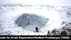 Russia -- A scientist climbs down to the bottom of a crater with the depth of 200 meters on Yamal Peninsula, November 9, 2014