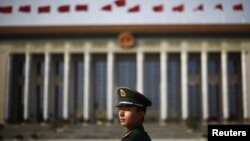 A Chinese paramilitary police officer stands in front of the Great Hall of the People at Beijing's Tiananmen Square. (file photo)