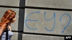 "A woman in downtown Belgrade walks past graffiti that says ""EU?"""