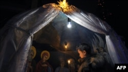 A boy holds a candle during an Orthodox service in a church in Bishkek, Kyrgyzstan, on Christmas eve.
