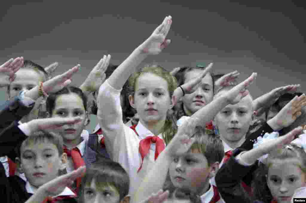Russian children wearing red neckerchiefs, a symbol of the Pioneer Organization, salute while posing for a picture during a ceremony for the inauguration of 18 newly adopted members at a school in the Stavropol region. (Reuters/Eduard Korniyenko)