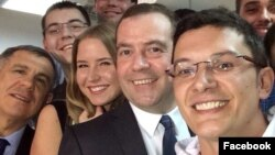 Ramil Ibragimov (right) takes a photo with Russian Prime Minister Dmitry Medvedev.