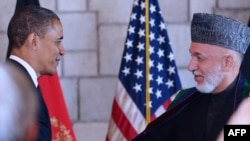 Afghan President Hamid Karzai (right) shakes hands with U.S. President Barack Obama after signing the accord in Kabul.